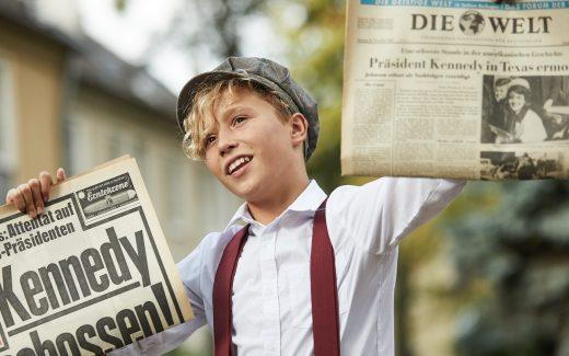 Zeitungsjunge mit Bild & Welt Schlagzeile